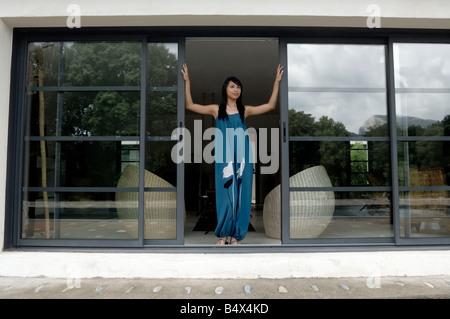 Woman opening front door - Stock Photo
