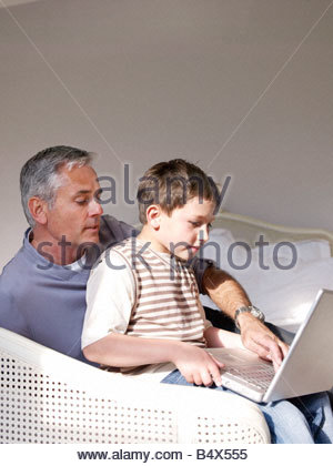 Father and son on laptop in bedroom - Stock Photo