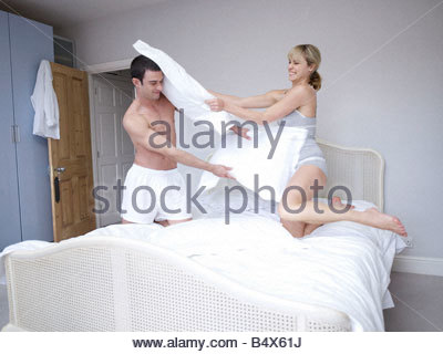 Man and woman bedroom pillow fight - Stock Photo
