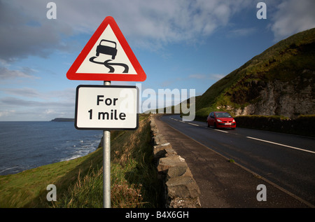 car travelling past the slippery road danger red warning triangle for 1 mile sign on the famous A2 north antrim - Stock Photo