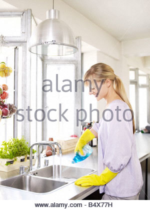 Woman in kitchen at sink cleaning - Stock Photo