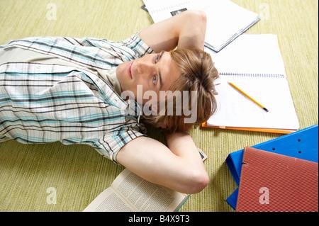 Young man lying on rug - Stock Photo