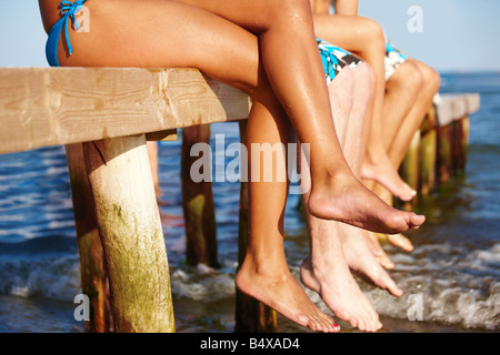 Young friends sitting on dock - Stock Photo
