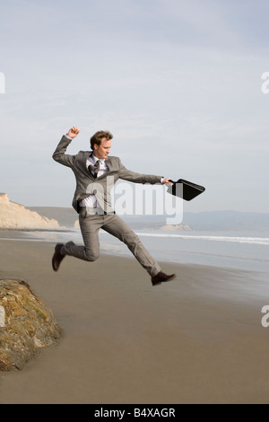 Businessman jumping on beach - Stock Photo