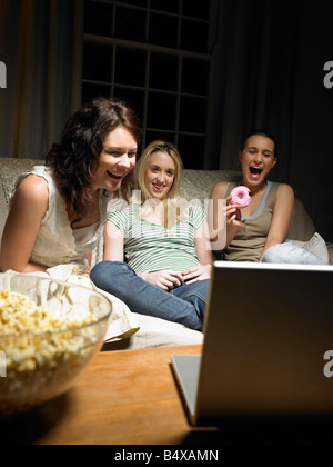 Three young women watching a movie - Stock Photo