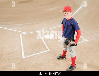 Baseball player in uniform posing by home plate - Stock Photo