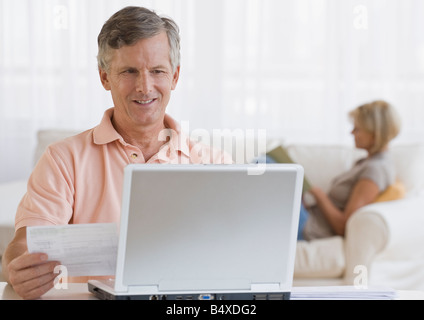 Man paying bills online - Stock Photo