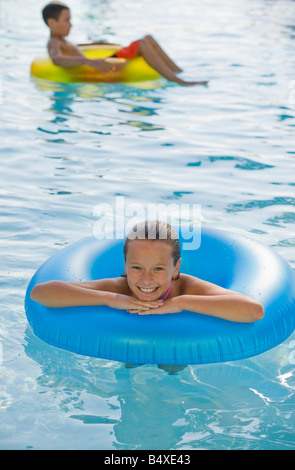 Children playing with inflatable tubes in swimming pool - Stock Photo