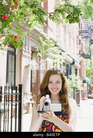 Woman holding video camera in urban setting - Stock Photo