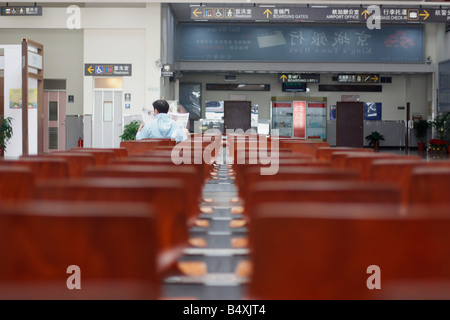 Lone man waiting in a small domestic airport. - Stock Photo