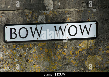 Street sign reading Bow Wow on a wall of cotswold stone, South Cerney, Gloucestershire near Cirencester - Stock Photo