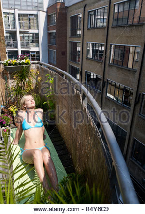 Woman sunbathing on city balcony - Stock Photo