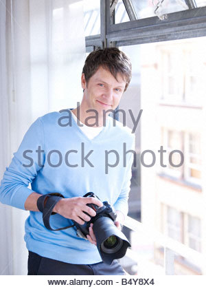 Man by window with digital camera - Stock Photo