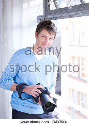 Man by window with digital camera - Stock Photo