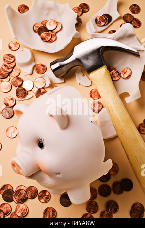 Broken piggy bank with hammer and pennies - Stock Photo