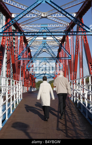 An Elderly couple cross the Detroit Bridge Salford Quays - Stock Photo
