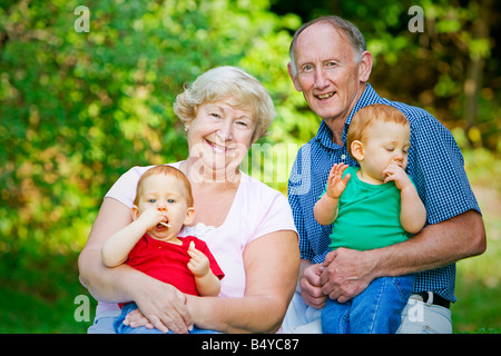Holding redheaded twin grandsons with focus on happy grandparents - Stock Photo