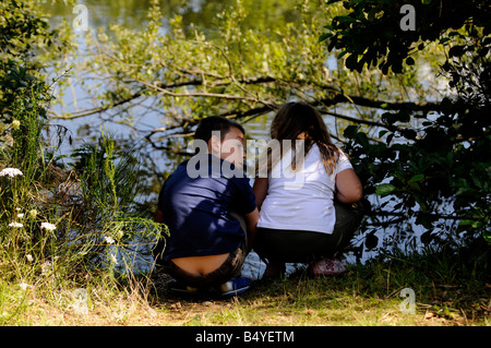 Brother and sister looking in a lake at Belhus Park - Stock Photo