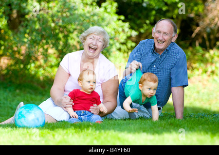 Playing with redheaded twin grandsons with focus on laughing grandparents - Stock Photo