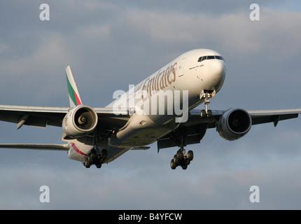 Emirates Boeing 777-300 landing at sunset - Stock Photo