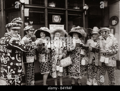 Pearly Kings and Queens celebrate Covent Gardens 300th Birthday Costers Hats Buttons Holding Beer Glasses Collecting - Stock Photo