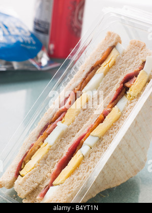 Egg And Bacon Sandwich On White Bread With A Bag Of Crisps And A Can Of Fizzy Drink - Stock Photo