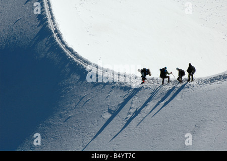 Mountain climbers ascend a tricky snow covered ridge on Mont Blanc in the French Alps - Stock Photo