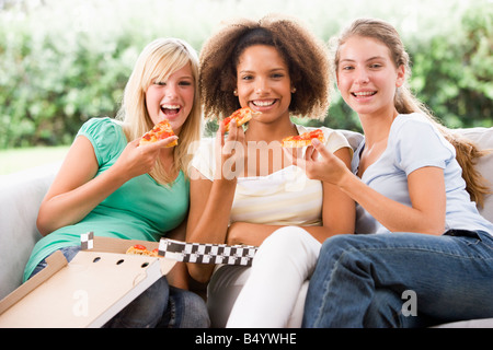 Teenage Girls Sitting On Couch And Eating Pizza Together - Stock Photo