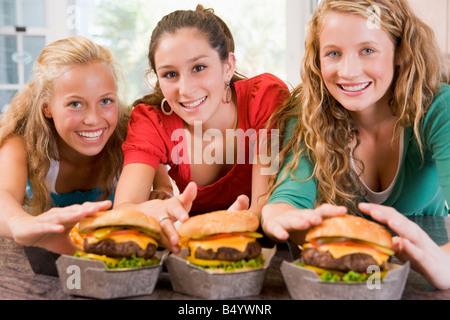 Teenage Girls Eating Burgers - Stock Photo