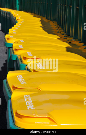Lots of recycling bins or wheelie bins lined up in a row with bright yellow lids - Stock Photo