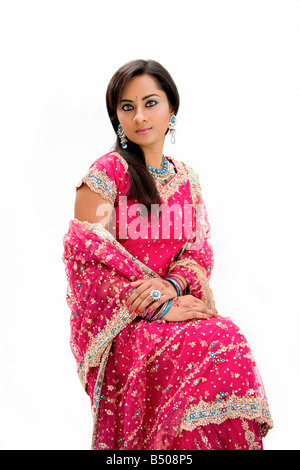 Beautiful Bangali bride in colorful dress sitting isolated - Stock Photo