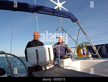 Skipper and his mate helming yacht Namaste at sea on a bright sunny day - Stock Photo