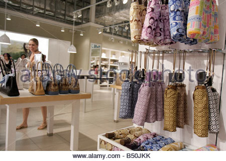 coachfactoryoutlet 95co  Lone Mexican elderly woman; Miami Florida Dolphin Mall Coach Factory Outlet  woman shopper shopping designer handbags leather goods brand marketing