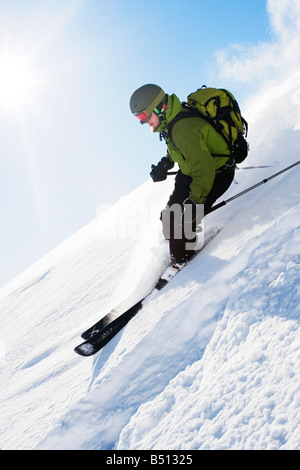 Low angle view of a young man skiing Alps Switzerland - Stock Photo