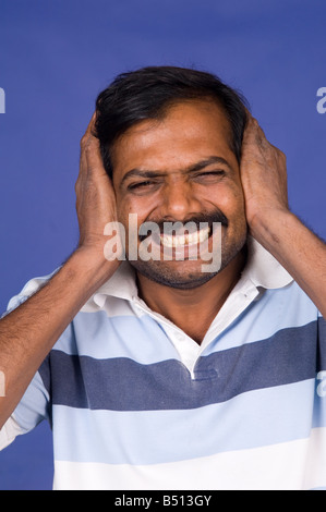 Indian man hands on ears - Stock Photo