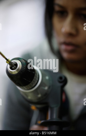 Asian woman uses electric drill to drive in a wood screw - Stock Photo