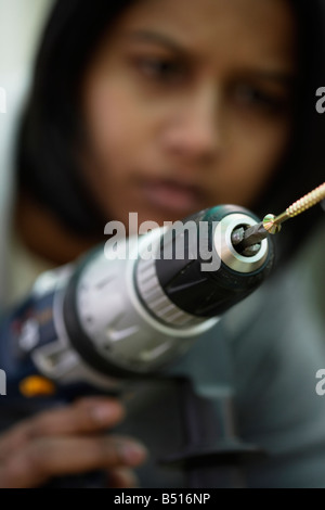 Asian woman uses electric drill to drive in a wood screw