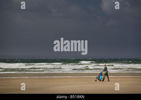 A man taking child for a walk in a pushchair on the beach (Brittany). Homme promenant un enfant sur la plage dans - Stock Photo