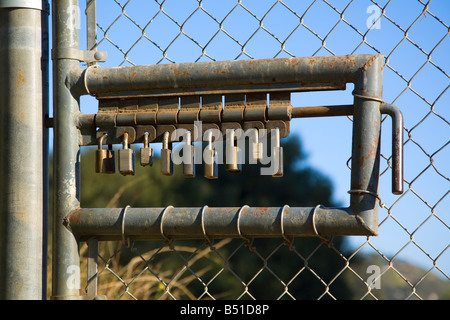 A true lock down concept, 9 pad locks make this gate to a restricted area a very secure barrier - Stock Photo