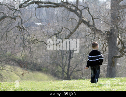 A little boy, clad in jeans and a heavy sweater, walks off across the grassy park on a cool, Spring day. - Stock Photo