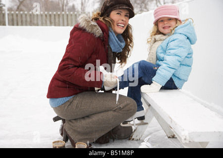 Mother Helping Daughter Put on Ice Skates - Stock Photo