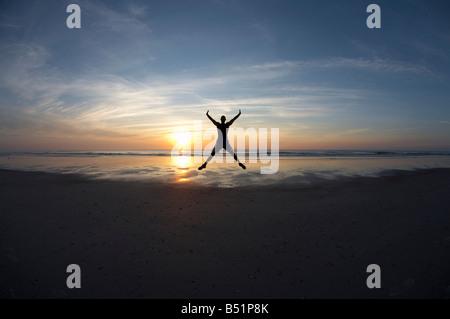 Man Jumping on Beach - Stock Photo