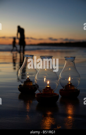 Oil Lamps on Beach at Sunset, People in Background - Stock Photo