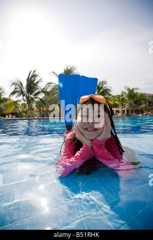 Portrait of Girl Lying in Swimming Pool Wearing Goggles and Flippers - Stock Photo