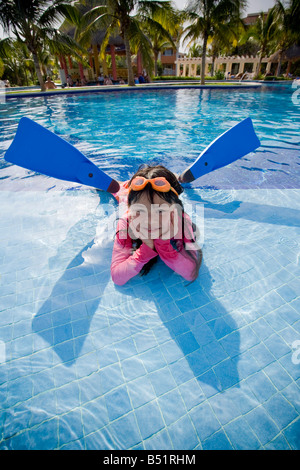 Girl Lying in Swimming Pool Wearing Goggles and Flippers - Stock Photo