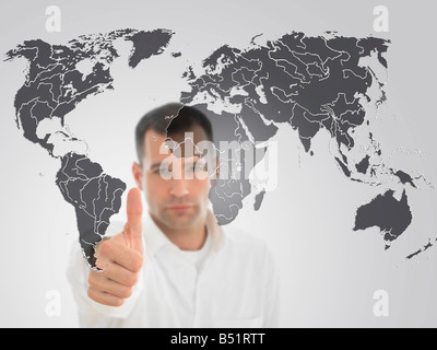 Portrait of Man Giving Thumbs Up in Front of World Map - Stock Photo