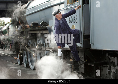 A steam engine driver climbs into his cab. The train is 60163 Tornado, on the Great Central Railway. - Stock Photo