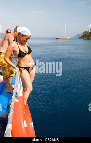 Female about to dive from a tour boat sailing around the 12 Islands near dalyan Turkey - Stock Photo