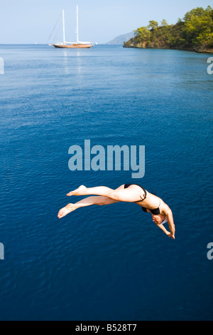 Female diving from a tour boat sailing around the 12 Islands near dalyan Turkey - Stock Photo