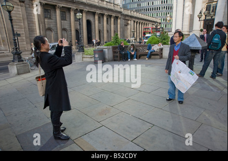 a woman Tourist takes a photograph of a man hold a map of London at the Royal Exchange, with the bank of England - Stock Photo
